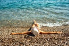 Jonge vrouw in een hoed en een bikini die op het strand in de hete zomer liggen Stock Foto