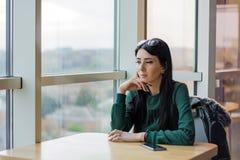 Jonge vrouw in een koffie dichtbij de lijst in afwachting van het onderzoeken van een groot venster stock afbeeldingen