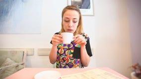Jonge vrouw in een koffie, het drinken koffie stock footage