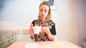 Jonge vrouw in een koffie, het drinken koffie stock video