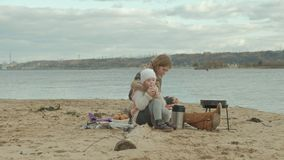 Jonge vrouw in een laag met een meisje met krullend haar, mamma en dochter, die op het strand door de rivier, oceaan zitten, die  stock footage
