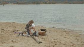 Jonge vrouw in een laag met een meisje met krullend haar, mamma en dochter, die op het strand door de rivier, oceaan zitten, die  stock videobeelden
