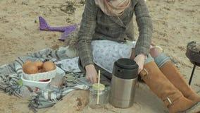 Jonge vrouw in een laag met een meisje met krullend haar, mamma en dochter, die op het strand door de rivier, oceaan zitten, die  stock video