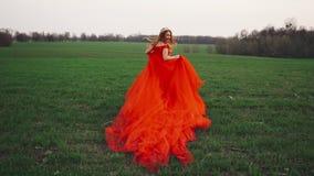 Jonge vrouw in een luxueuze rode kledingslooppas langs het groene gras stock footage