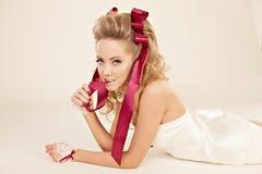 Jonge vrouw in een poppenstijl met rode bogen en flirty blikken Royalty-vrije Stock Foto's