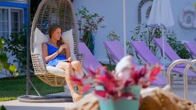 Jonge vrouw in een schommelstoel die nota's in het boek maken stock video