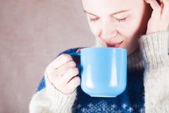 Jonge vrouw in een sweater met een mok heet of warm van koffie of thee Royalty-vrije Stock Afbeelding