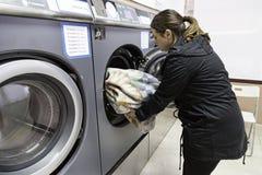 Jonge vrouw in een wasserij Stock Foto's