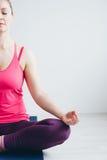 Jonge vrouw in een witte ruimte die yogaoefeningen doen stock afbeeldingen