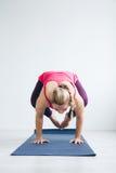 Jonge vrouw in een witte ruimte die yogaoefeningen doen stock fotografie