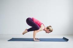 Jonge vrouw in een witte ruimte die yogaoefeningen doen stock foto's