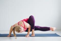 Jonge vrouw in een witte ruimte die yogaoefeningen doen royalty-vrije stock fotografie