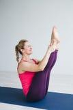 Jonge vrouw in een witte ruimte die yogaoefeningen doen royalty-vrije stock afbeeldingen