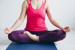 Jonge vrouw in een witte ruimte die yogaoefeningen doen stock afbeelding