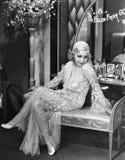 Jonge vrouw in een zitting van de avondtoga op een beklede bank (Alle afgeschilderde personen leven niet langer en geen landgoed  royalty-vrije stock foto's