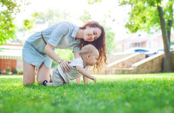 Jonge vrouw en babyzoon die de zomer van dag in park genieten royalty-vrije stock fotografie