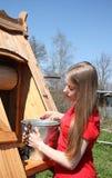 Jonge vrouw en de put met een emmer water Stock Foto's