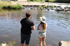 Jonge vrouw en een man terwijl visserij op een rivier in Beieren Stock Foto