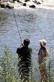 Jonge vrouw en een man terwijl visserij op een rivier in Beieren Stock Afbeelding