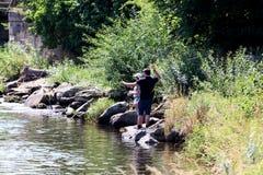 Jonge vrouw en een man terwijl visserij op een rivier in Beieren Stock Fotografie