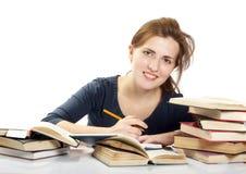 Jonge vrouw en een stapel van boeken stock afbeelding