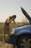 Jonge vrouw en gebroken auto stock foto
