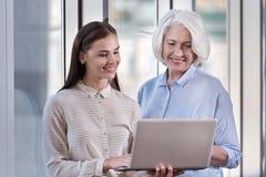 Jonge vrouw en haar bejaarde werkgever die aan laptop samenwerken Royalty-vrije Stock Foto