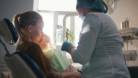 Jonge vrouw en haar dochter bij het onderzoek bij de tandarts stock video