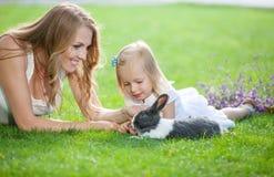 Jonge vrouw en haar dochter die met een huisdierenkonijn spelen stock afbeelding