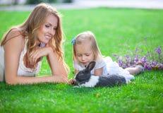 Jonge vrouw en haar dochter die met een huisdierenkonijn spelen in een park stock fotografie