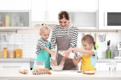 Jonge vrouw en haar dochters het koken stock foto's