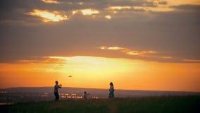 Jonge vrouw en haar echtgenoot het spelen frisbee op het gebied, die zich naast hun kleine zoon, de avond van de zonsondergangzom stock footage