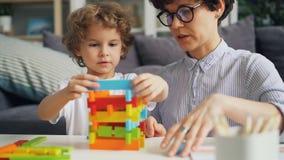 Jonge vrouw en haar klein kind die met houtconstructieblokken thuis spelen stock footage