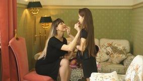 Jonge vrouw en haar weinig dochter die make-up thuis toepassen stock footage