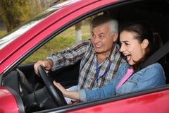 Jonge vrouw en hogere instructeur in auto Ontbreek rijbewijs royalty-vrije stock fotografie