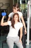 Jonge vrouw en instructeur in de gymnastiek Stock Afbeelding