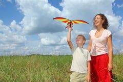 Jonge vrouw en jongensspelenvlieger op weide stock afbeelding