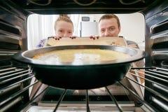 Jonge vrouw en jonge man die kaastaart in oven bekijken royalty-vrije stock fotografie