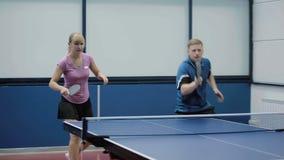 Jonge vrouw en man die samen in een pingpong spelen stock videobeelden
