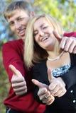 Jonge vrouw en man glimlach en duim omhoog in park royalty-vrije stock foto's