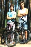 Jonge vrouw en man met fietsen Stock Foto