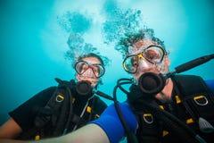 Jonge vrouw en man scuba-duikers die selfie maken stock afbeeldingen