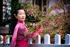 Jonge vrouw en roze begonia Stock Foto's