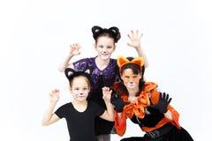 Jonge vrouw en twee meisjes in de kostuums van kattencarnaval het stellen Stock Fotografie