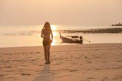 Jonge vrouw en vissersboot in zonsondergang Stock Afbeelding