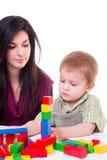 Jonge vrouw en weinig jongen die houten kubussen spelen Stock Foto