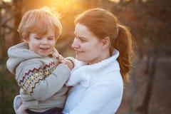 Jonge vrouw en weinig zoon die in avondlicht koesteren Royalty-vrije Stock Fotografie
