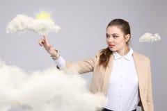 Jonge vrouw en zon die uit van achter de de wolken, wolk gegevensverwerking of het weerconcept glanzen stock afbeelding