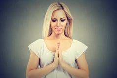 Jonge vrouw in gebedpositie het mediteren stock afbeeldingen