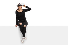 Jonge vrouw gebruikend virtuele werkelijkheidshoofdtelefoon en zittend op paneel royalty-vrije stock afbeelding
